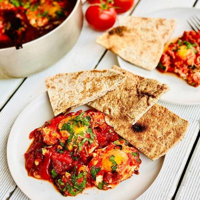 Shakshuka on two white plates with pieces of flatbread on the edge of the plates and a bunch of fresh tomatoes at the top middle of the picture and a glimpse of the pan with shakshuka in on the top left corner of the picture