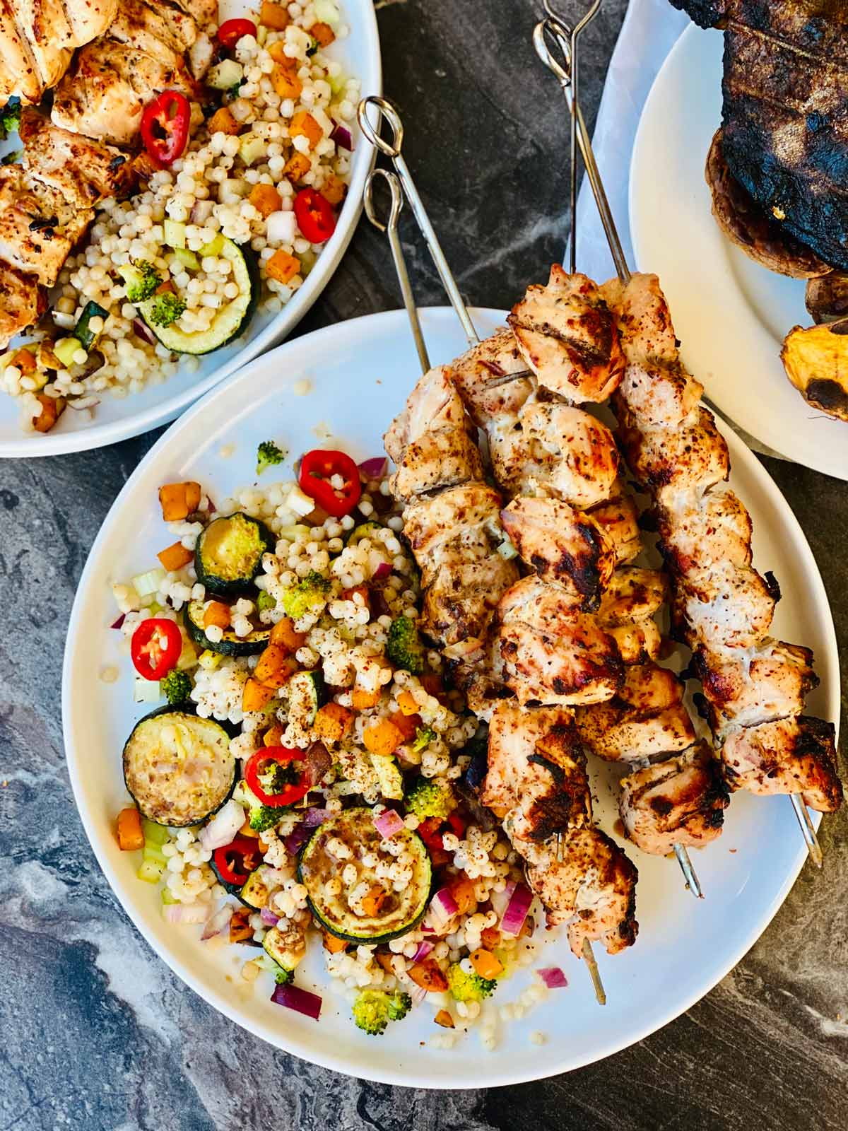 4 Chicken kebabs on a white plate with mixed vegetable couscous