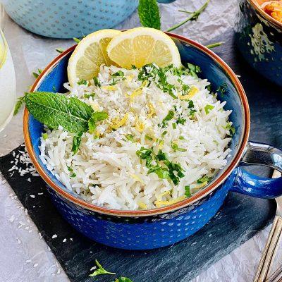 Instant pot coconut rice in a blue serving bowl garnished with lemon, lemon rind and mint
