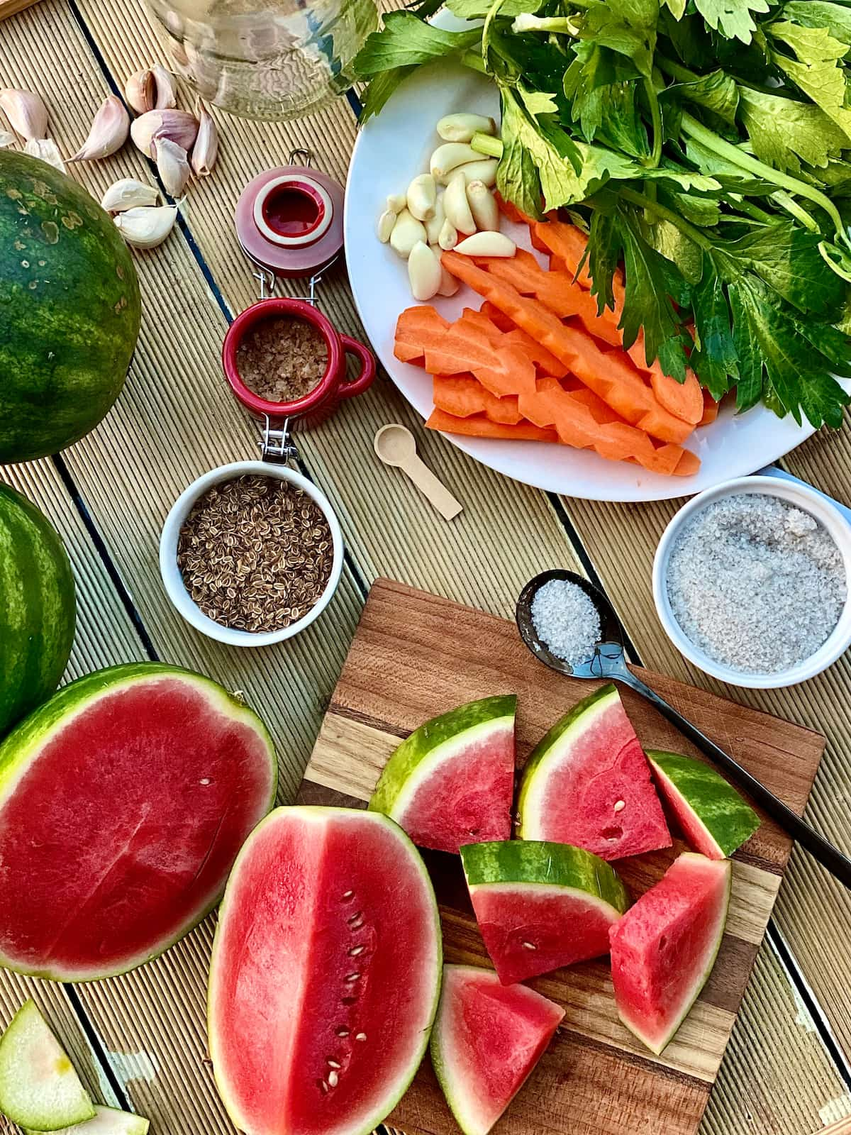 Fresh watermelon sliced and quartered for pickling, salt in a tiny dish, dill seeds and carrot, garlic cloves, celery leaves, on a white plate