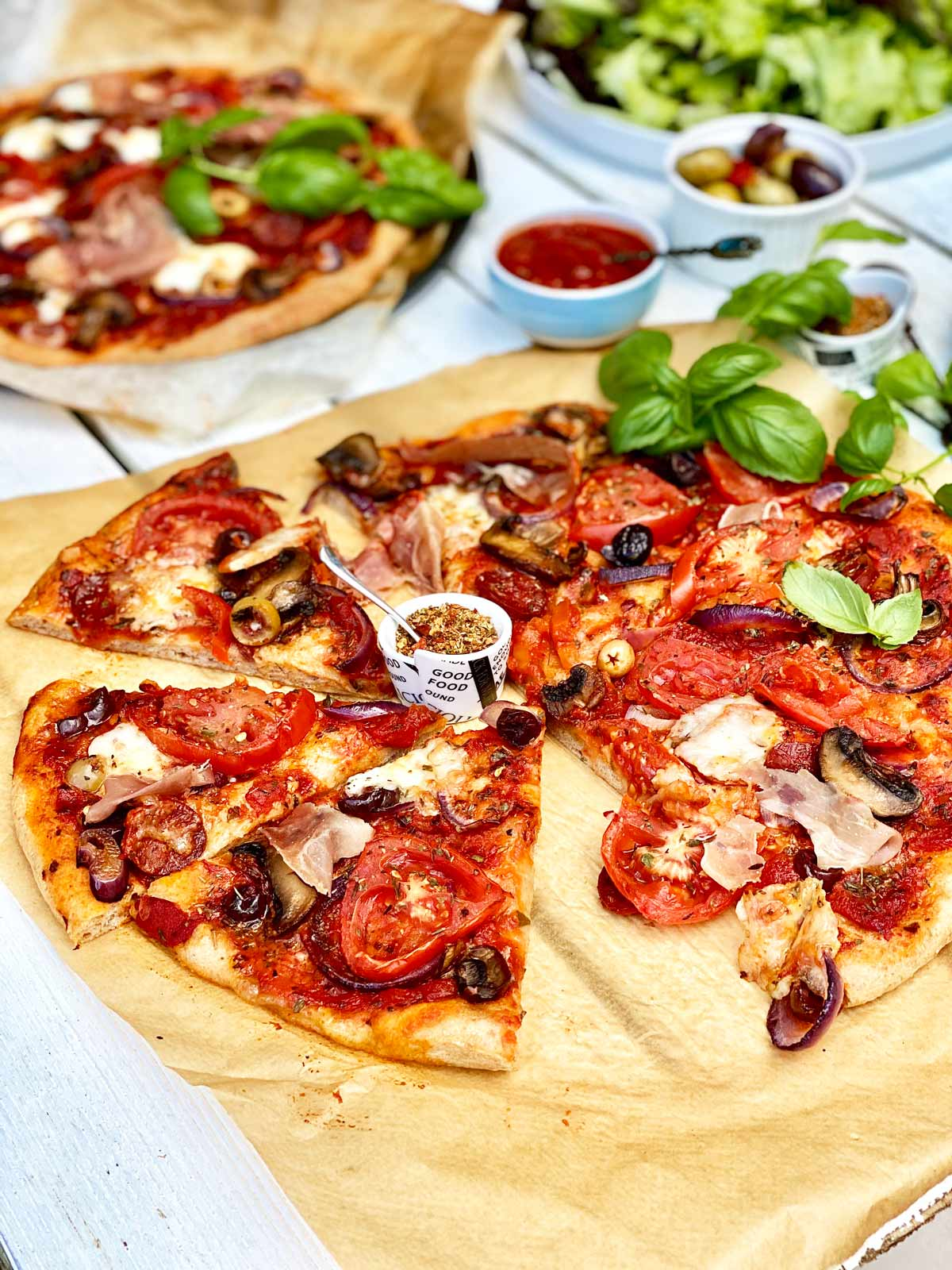Homemade pizza on brown parchment paper without a slice