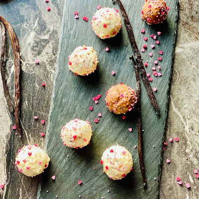 Cake pops on a black slate placemat with four vanilla pods and scattered little pink sugar hearts