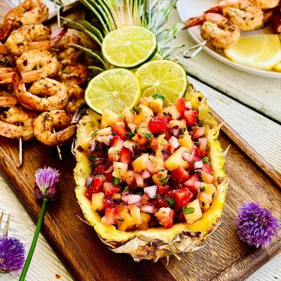 Pineapple mango salsa in a fresh pineapple boat topped with three lime slices