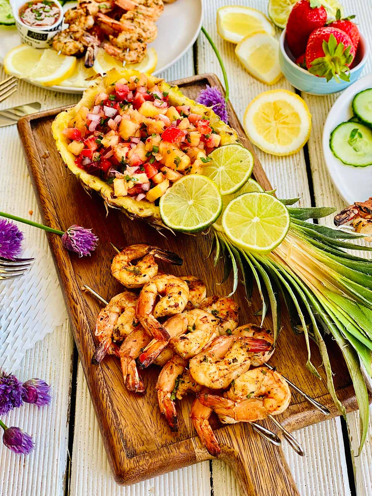 Pineapple mango salsa on a wooden board with grilled prawns next to it