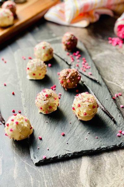 milk and chocholate cake pops on a black slate with two vanilla pods and scattered little pink sugar hearts