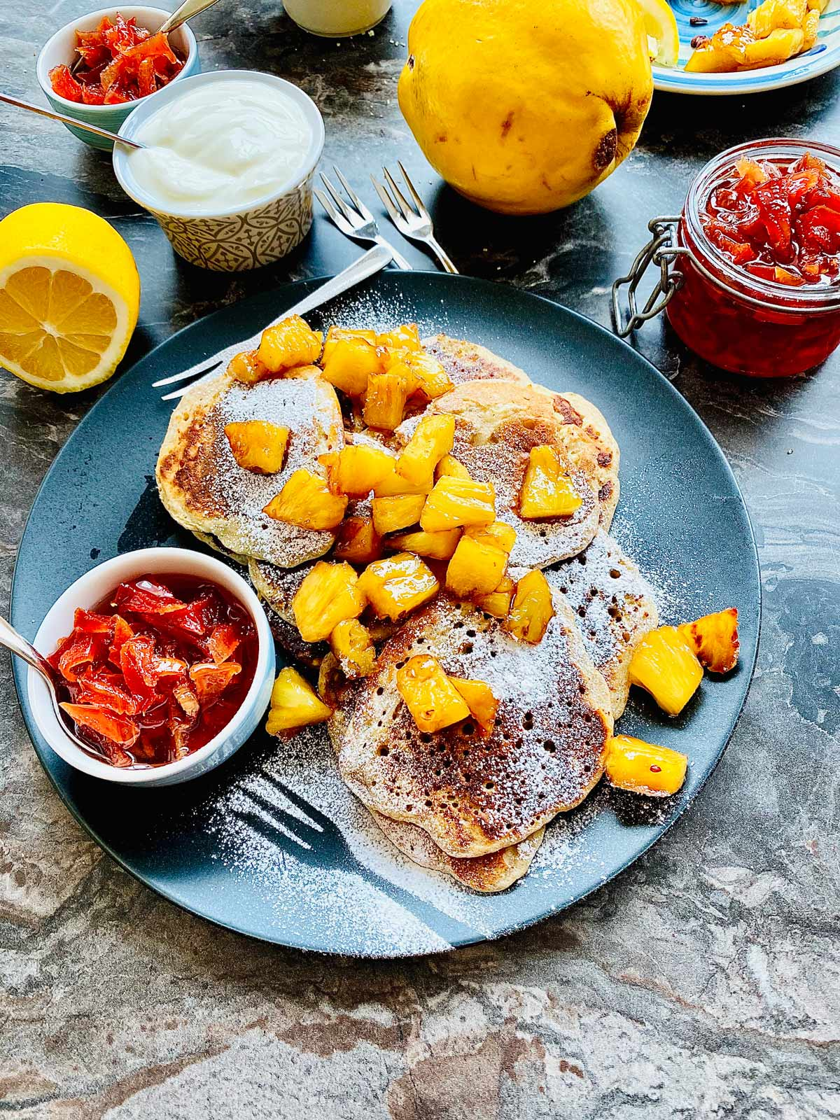 ricotta pancakes topped with chopped pineapple and a small serving dish with jam on a black plate