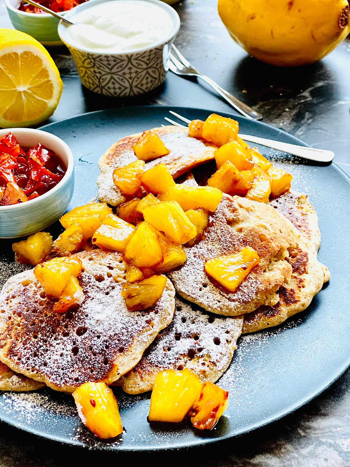 a few ricotta pancakes topped with pineapple chunks and a small dish on the left with a reddish chunky jam all on a black plate