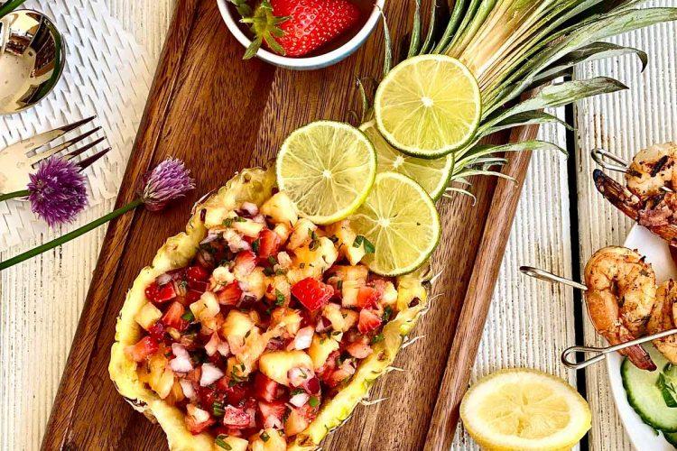 Pineapple mango salsa in freshly cut pineapple boat on a dark wooden board