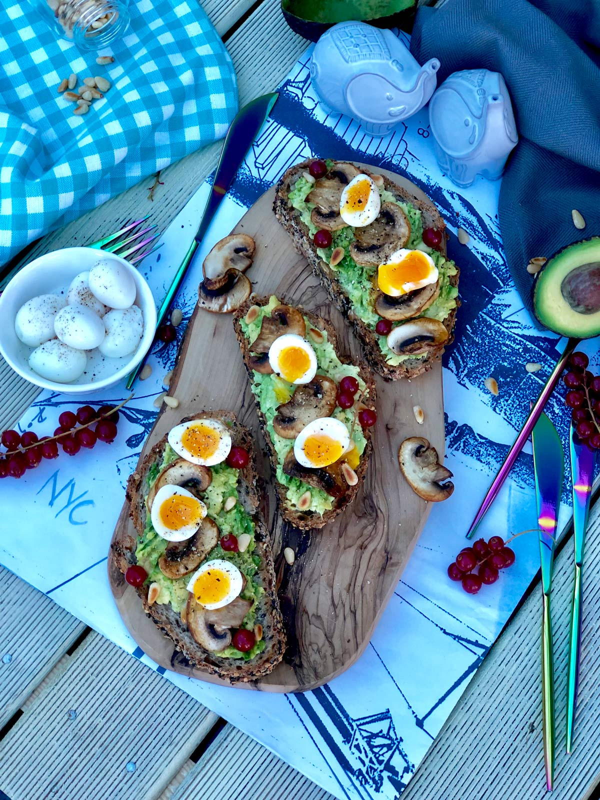 Soft boiled quail eggs, crushed avocado and red currants on seeded sourdough toast