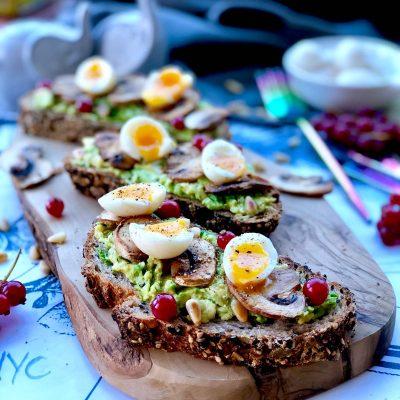 Soft boiled quail eggs, avocado butter and redcurrant on sourdough toast