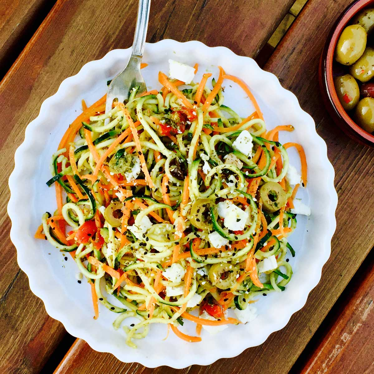 Vegetarian pesto courgette and carrot noodles with feta cheese and olives