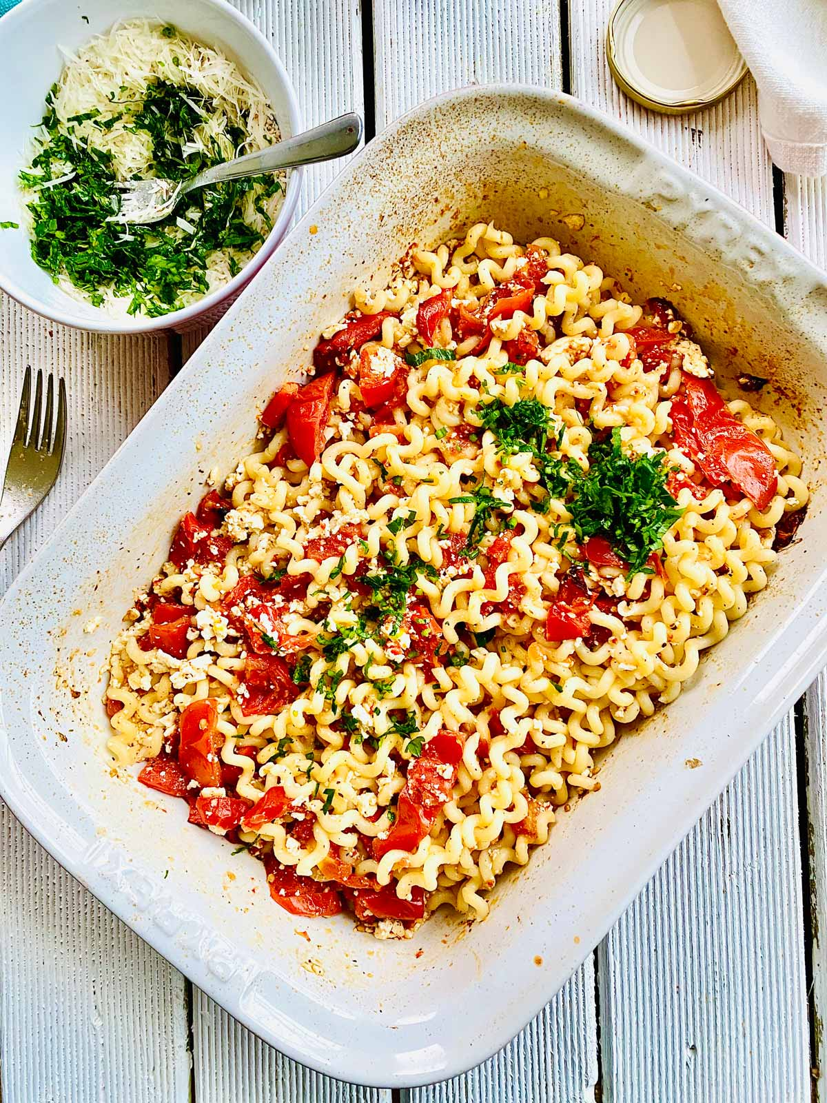 Pasta mixed with roast feta, tomatoes and fresh herbs in an ovenproof dish