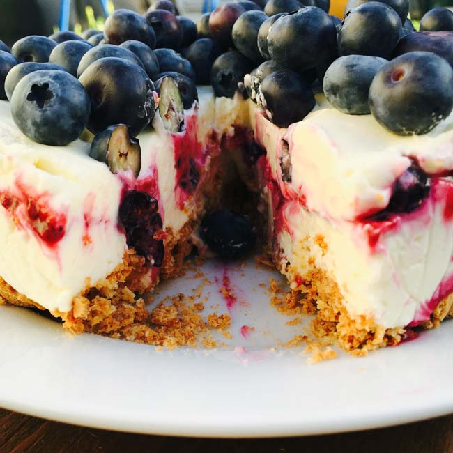 A cheese cake with berries & amaretti, sliced