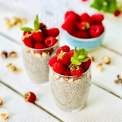 Chia pudding with nuts and raspberries in a glass