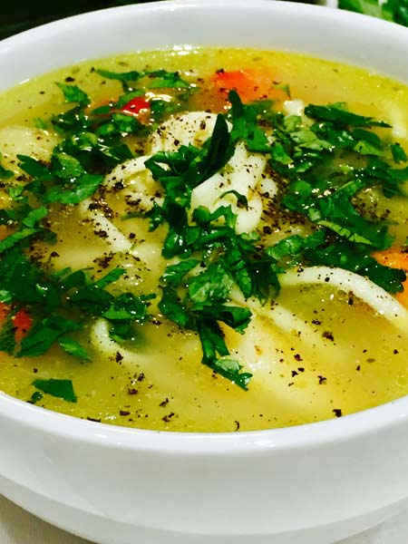 A close-up of a tasty and comforting chicken soup, in a white plate.