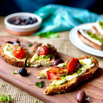 Cream cheese and pesto bruschetta with fresh basil flowers