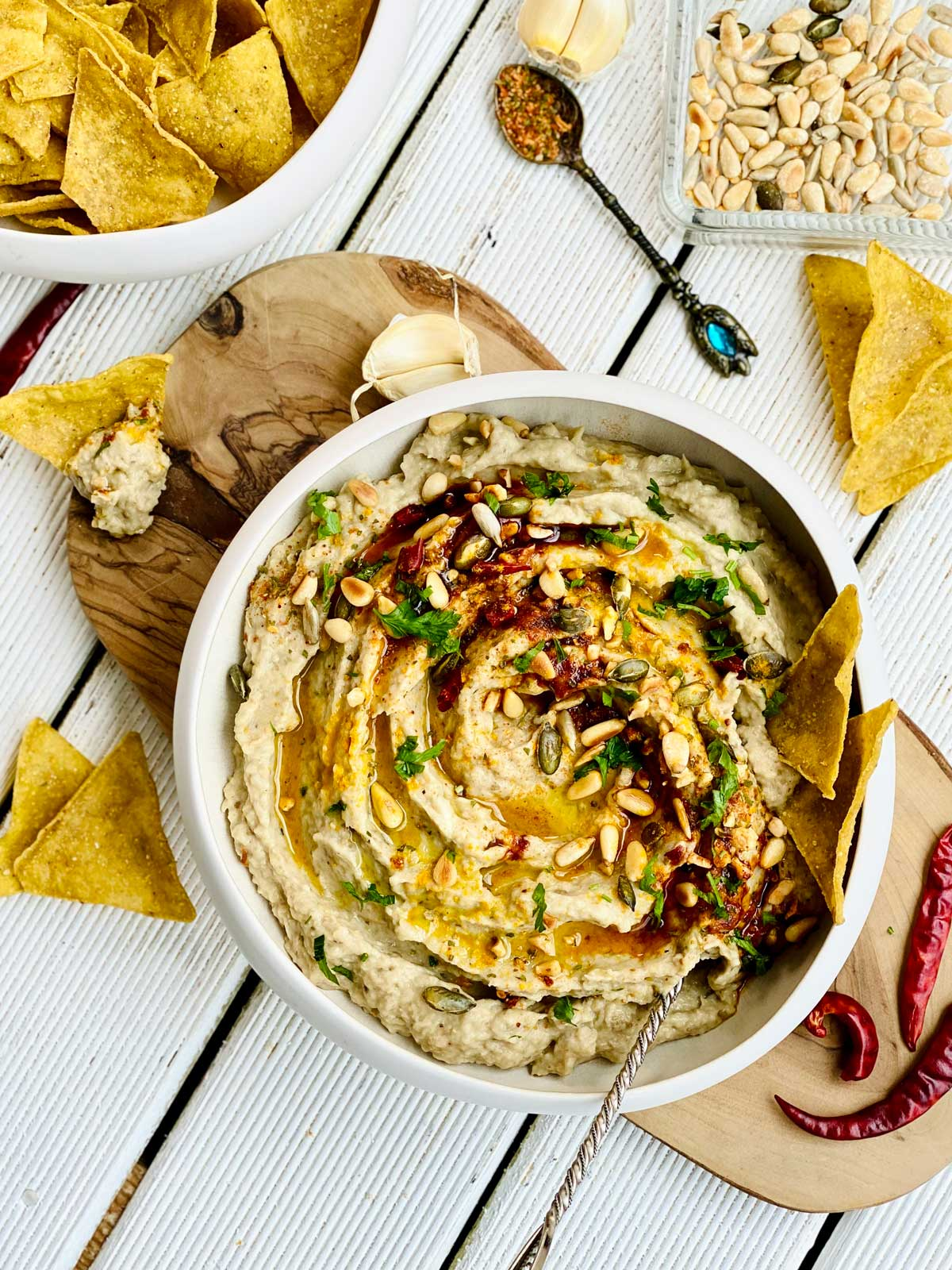 Creamy eggplant dip spread birdsview in an ivory deep plate placed on a wooden board with red chillies and tortilla chips scattered around the sides