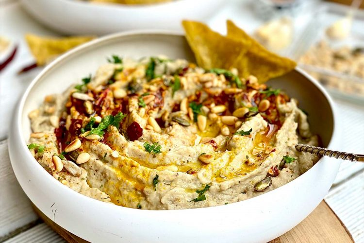 Close up of creamy eggplant dip topped with paprika, seeds and fresh herbs and olive oil