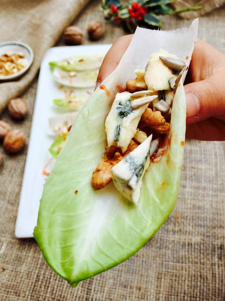Close-up of an endive 'boat' full of delicious blue cheese, date syrup and walnuts.