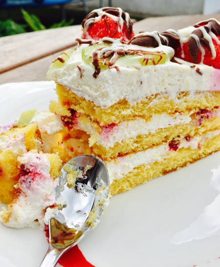 A slice of delicious fruit and cream cake.