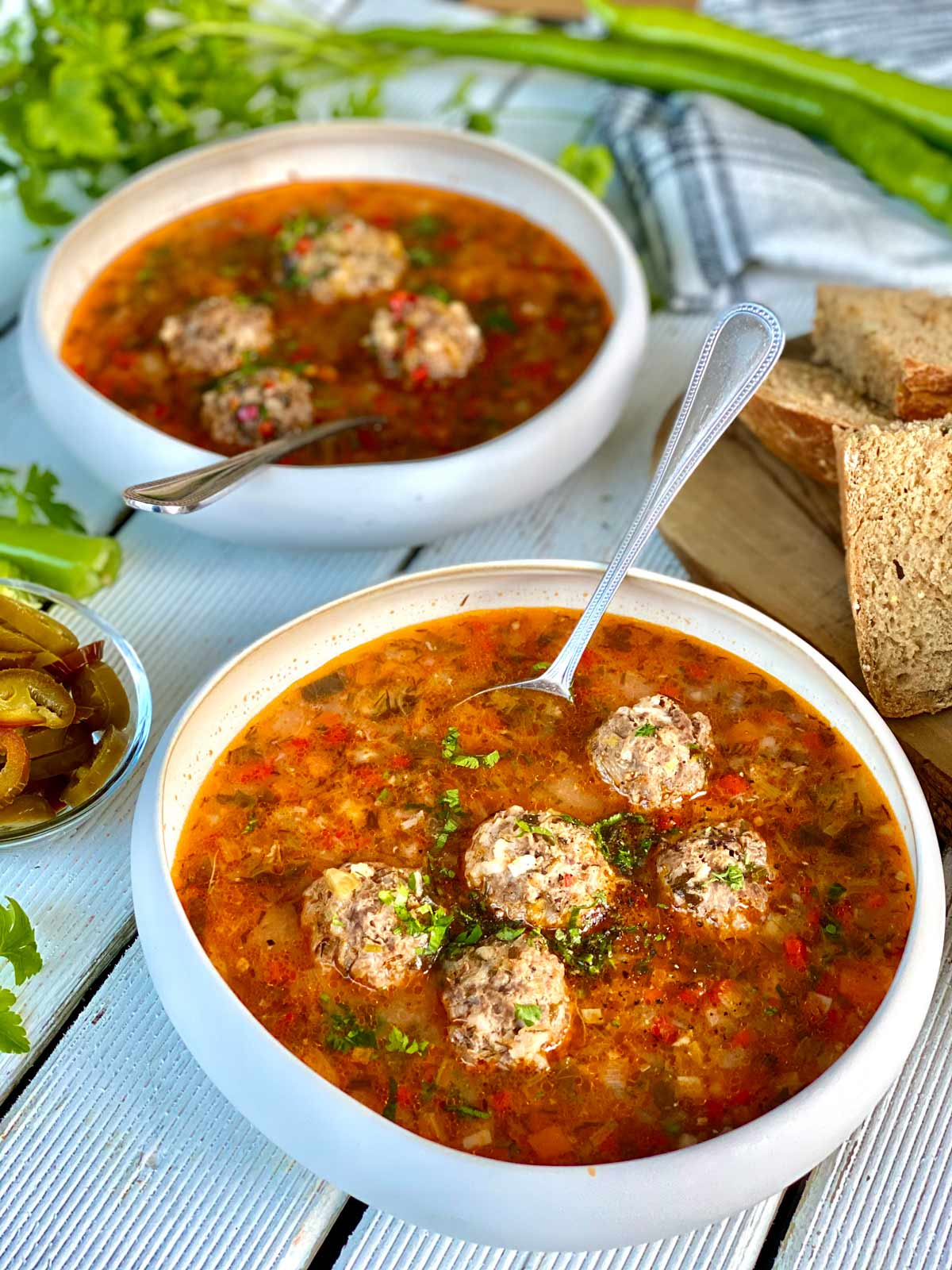 2 meatballs soup bowls, a glimpse of wholemeal bread slices on a chopping board on the right a kitchen towel and green peppers and fresh herbs in the far end