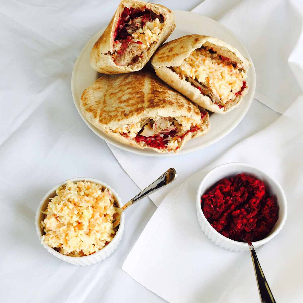 Three lamb pita pockets (sandwiches), alongside bowls of coleslaw and horseradish sauce