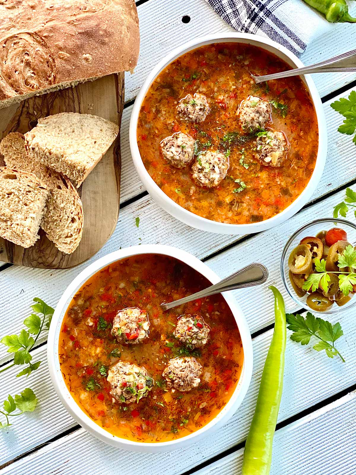 two white bowls with meatballs soup and spoons in with bread slices on the left and a small serving dish on the right filled with pickled jalapenos some fresh parsley leaves scattered around and a green pepperright