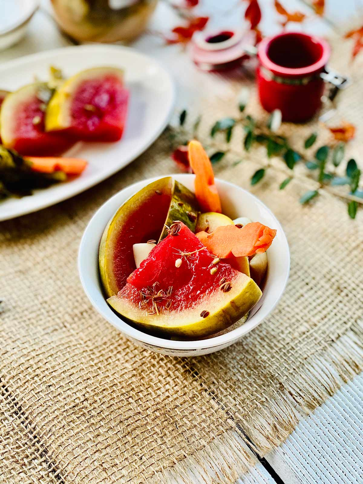 Pickled watermelon quarter slices with pickled carrot in a white serving dish
