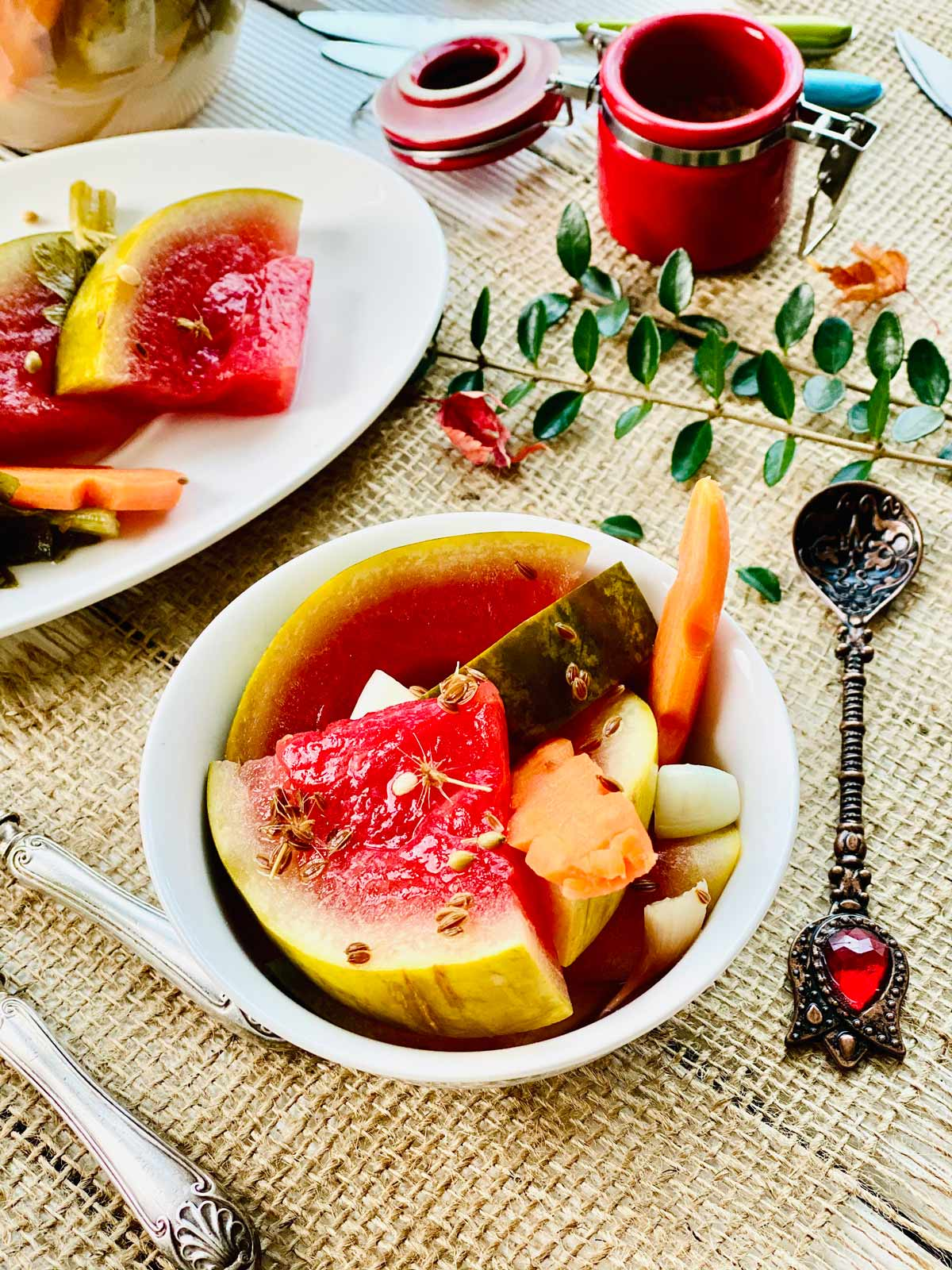 Pickled watermelon slices with pickled carrot in a white serving dish and a few more slices at the back top left side in an oval white plate