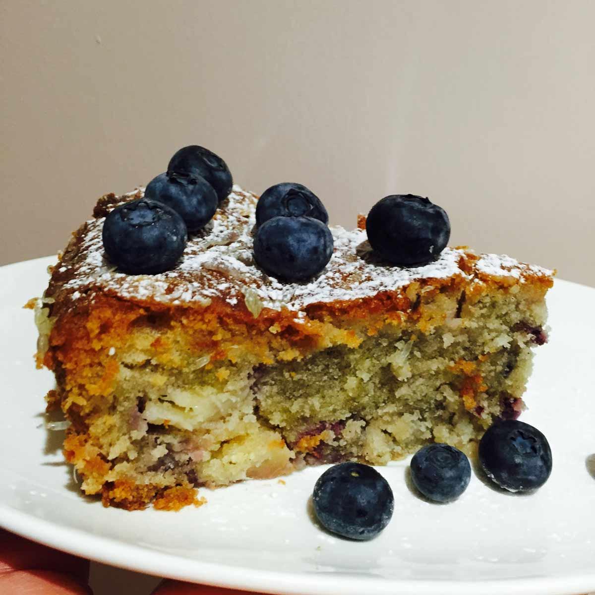 A slice of pineapple, berries & coconut cake