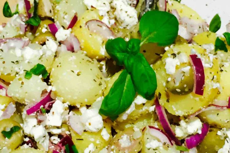 A bowl full of delicious potato, olives and feta cheese salad.