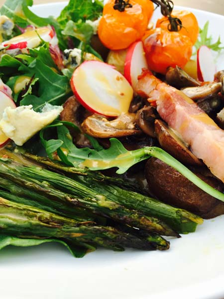 A close-up of the delicious potato roast, with a small arrangement of grilled asparagus and cherry tomatoes.