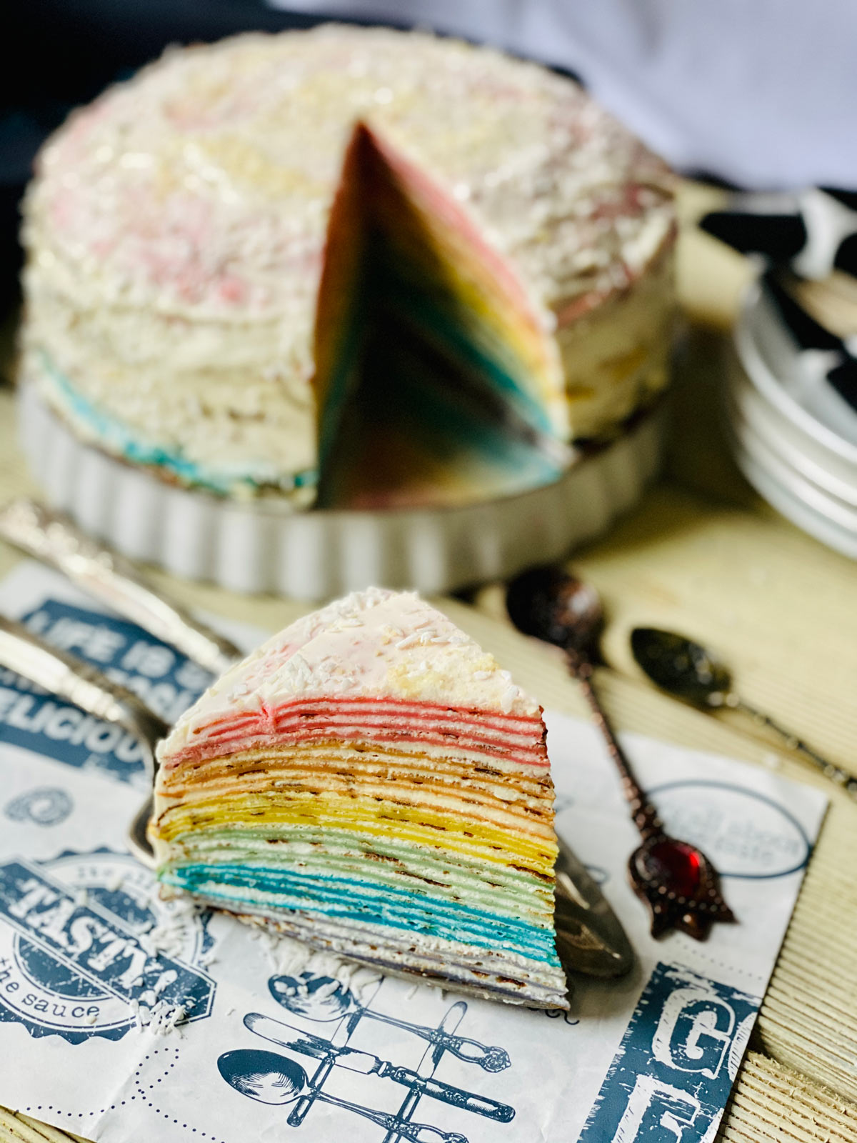 Rainbow crepe cake slice close up on patterned paper