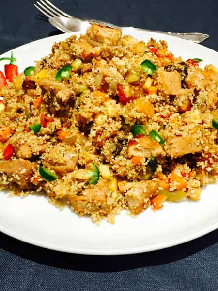 A white plate with delicious couscous, mixed with chunks of roast pork.