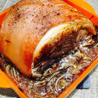 A chunky piece of roast pork, on a bed of beer and onions.