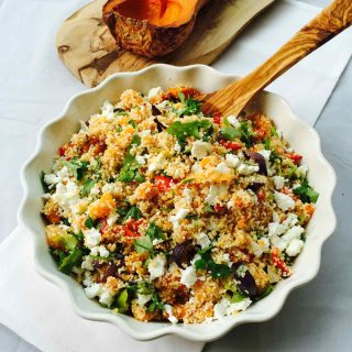 A white bowl with roasted veggies & feta couscous