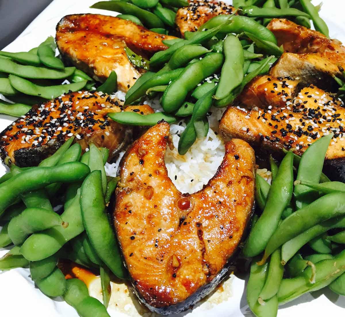 Salmon teriyaki with edamame and rice, on a white plate