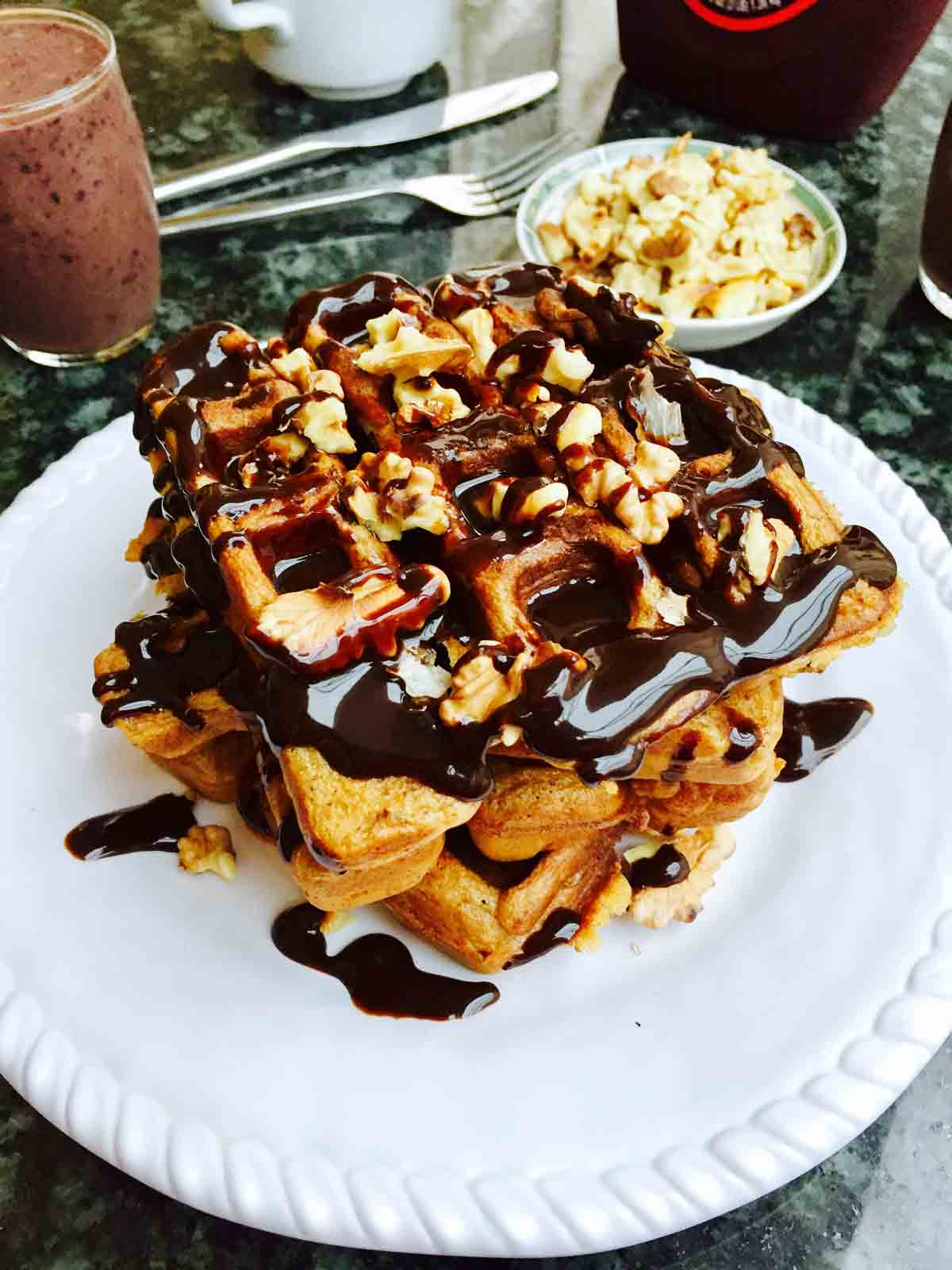 A white plate with scrumptious waffles, all covered in delicious chocolate sauce.