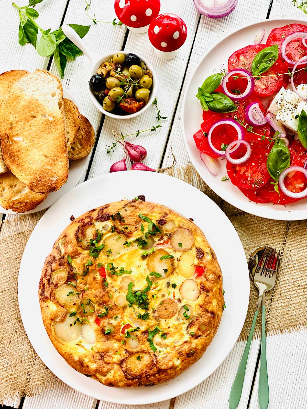 Spanish tortilla on a white plate, tomato salad on a white plate on the right mixed olives on top and toasted bread slices on smaller plate on the left