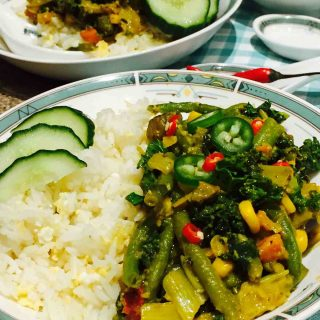 A white plate of scrumptious vegetarian curry, together with egg-fried rice and other veggies.