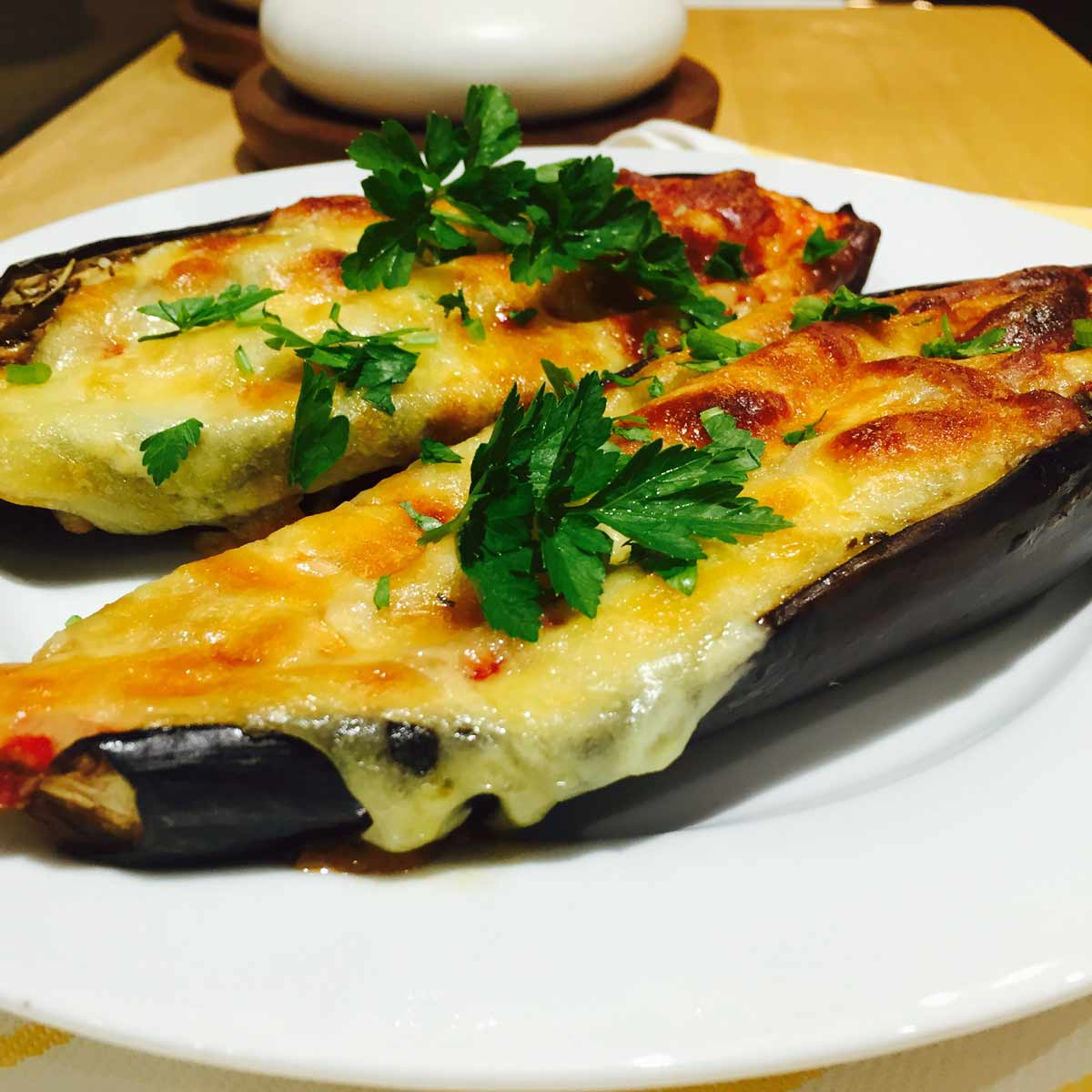Two Tomato & cheese topped aubergines, on a white plate