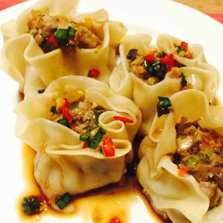 Veal steamed dumplings or dim sum on a white plate