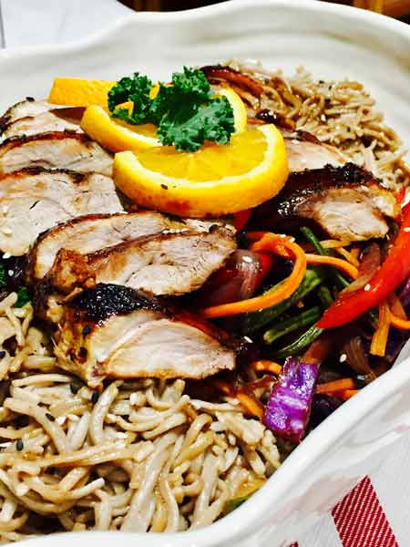 A white plate of delicious duck in buckwheat noodles, topped up with lemon slices and kale leaves.
